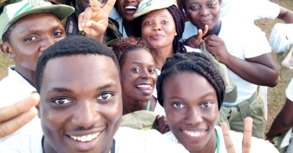 Corps members smiling while on camp