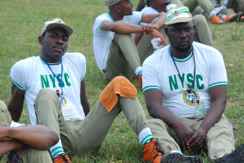 Two nysc friends sitting on the grass enjoying camp