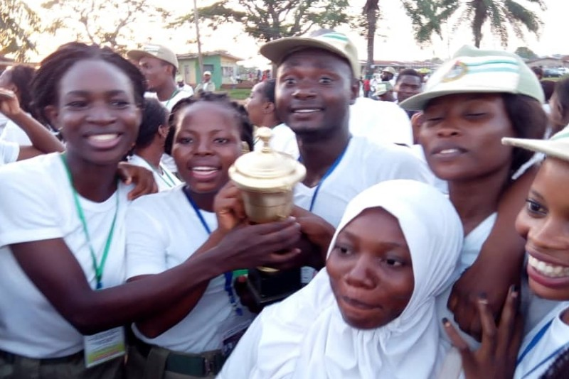 Corps member holding a cup of victory